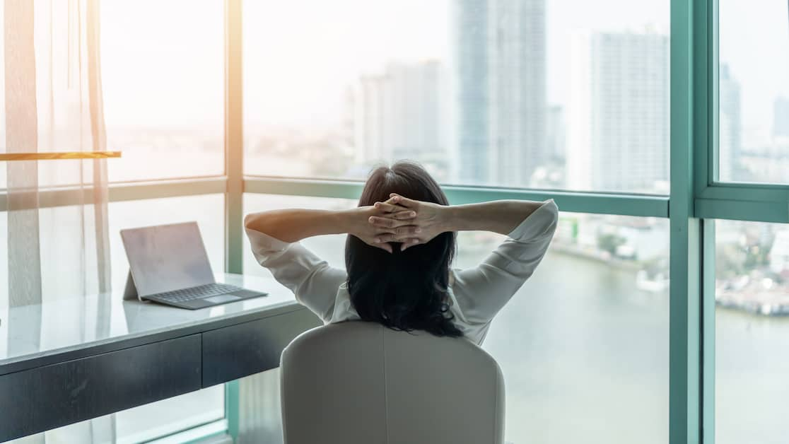 female-employee-with-healthy-work-life-balance-sitting-at-desk-looking-out-the-window