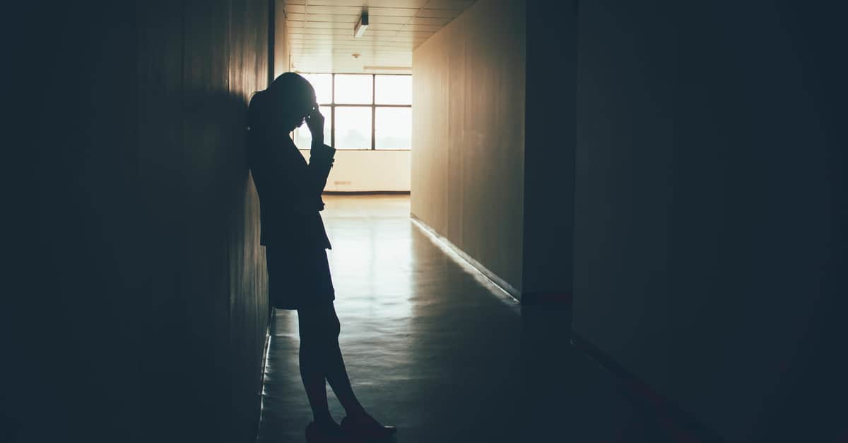 woman-managing-grief-and-loss-at-work-in-office-corridor